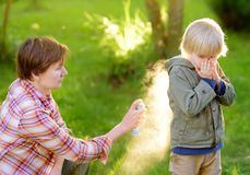 Woman spraying insect or mosquito repellents on little boy before a walk in the forest. Protect children from mosquitoes and other. Insects. Summer activities royalty free stock photos