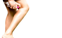 Woman spraying insect repellent on her leg isolated royalty free stock photo