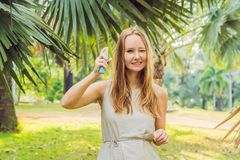 Woman spraying insect repellent on skin outdoor stock images