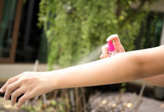 Woman spraying insect repellents on skin in the garden Royalty Free Stock Photos