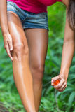 Woman spraying mosquito repellent on leg skin Stock Photos