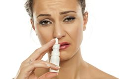 Woman spraying nasal drops. Young sad woman spraying nasal drops in her nose Stock Photos
