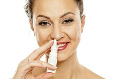 Woman spraying nasal drops. Young smiling woman spraying nasal drops in her nose Royalty Free Stock Photography