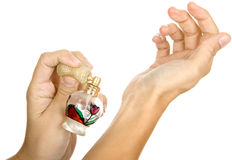 Woman spraying parfume. On hands royalty free stock images