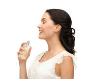 Woman spraying pefrume on her neck Stock Image