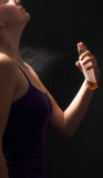 Woman spraying perfume. Woman in purple singlet spraying perfume Stock Photography