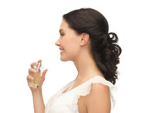 Woman spraying perfume on her neck stock images