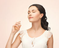 Woman spraying perfume on her neck Royalty Free Stock Photography