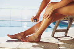 Woman spraying suntan lotion onto her leg by the pool. Woman sitting on deck chair by the swimming pool spraying suntan lotion onto her legs Stock Images