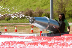 Woman Sprays Foamy Bubbles At Crazy Obstacle Race Stock Image