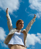 Woman spreading arms to sky Stock Photo