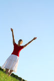 Woman spreading arms to sky. Happy young woman with arms outstretched Stock Image