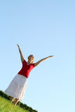 Woman spreading arms to sky. Happy young woman with arms outstretched Royalty Free Stock Image