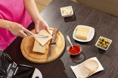 Woman spreading butter over a bread slice royalty free stock photography