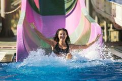 Woman spreading hands having fun on the water slide. Pretty brunette slim woman with spreading hands on the rubber ring having fun coming down on the purple royalty free stock photo