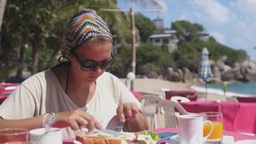 Sad woman in sunglasses spreads bread toasts with Butter in Beach Restaurant at the Sea. Tasty American breakfast near. Woman spreads toast with Butter in Beach stock video