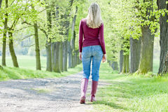 Woman in spring alley. Woman wearing rubber boots walking in spring alley Stock Photo
