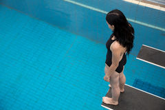 Woman on spring board at public swimming pool. Woman on diving board at public swimming pool being afraid to jump Royalty Free Stock Photo