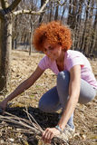 Woman spring cleaning the orchard. Caucasian woman spring cleaning the orchard, gathering cut branches to throw them away Stock Photo