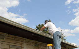 Woman spring cleaning rain gutters Stock Photo
