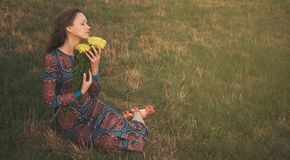Woman with spring flowers sitting on a grass stock photos