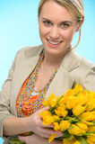 Woman with spring flowers yellow tulips Stock Photos