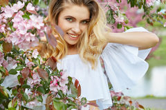 Woman in the spring garden among apple blossom. Royalty Free Stock Image