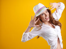 Woman with spring hat against yellow background Royalty Free Stock Images