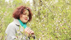 Woman in Spring Park. Pretty romantic young red head woman with cherry blossom in spring park. Spring trees background. Portrait close up stock video