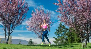 Woman in spring running or jogging as sport stock photos