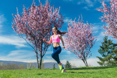 Woman in spring running or jogging as sport. In spring park royalty free stock image