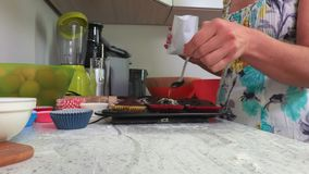 Woman sprinkle the top of the cupcake with powdered sugar. In room stock video footage