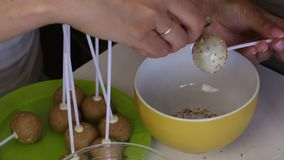 A woman sprinkles popcake with white chocolate in a colored dressing. Next on the table are ingredients for making popcakes. A woman sprinkles popcake with stock footage