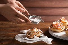 Woman sprinkling sugar powder on rose shaped apple pastry on wooden table stock photo