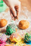 Woman sprinkling sugar strands on doughnuts. Woman`s hand sprinkling sugar strands on colorful doughnuts. Decoration stock image