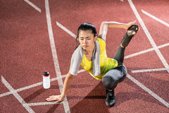 Woman sprinter doing warm up exercise before sprint Royalty Free Stock Photo