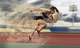 Woman sprinter leaving starting blocks royalty free stock photos