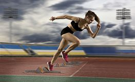 Woman sprinter leaving starting blocks on the athletic track Stock Photo