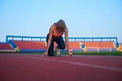 Woman  sprinter leaving starting blocks Stock Photography