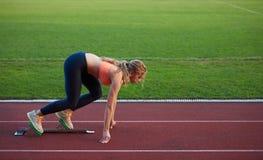 Woman  sprinter leaving starting blocks Stock Image