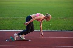 Woman  sprinter leaving starting blocks Royalty Free Stock Images