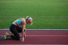 Woman  sprinter leaving starting blocks Royalty Free Stock Photo