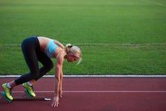 Woman  sprinter leaving starting blocks Royalty Free Stock Photography