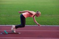 Woman  sprinter leaving starting blocks Stock Photo
