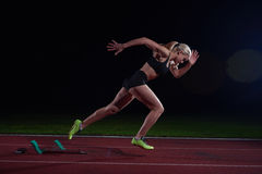 Woman  sprinter leaving starting blocks Royalty Free Stock Image