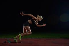 Woman  sprinter leaving starting blocks Royalty Free Stock Image