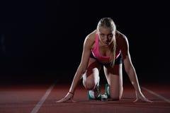 Woman  sprinter leaving starting blocks Stock Images