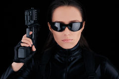 Woman Spy Holding Gun. Woman in a black leather suit holding a gun royalty free stock image