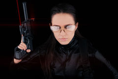 Woman Spy Holding Gun with Laser Sights. Woman in a black leather suit holding a gun with laser sights stock images