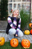 Woman squat at halloween pumpkins Royalty Free Stock Images